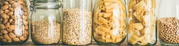 Uncooked cereals, grains, beans and pasta on table, wide composition. Various uncooked cereals, grains, beans and pasta for healthy cooking in glass jars on Royalty Free Stock Photos