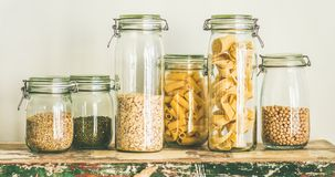 Uncooked cereals, grains, beans and pasta on table, wide composition. Various uncooked cereals, grains, beans and pasta for healthy cooking in glass jars on Royalty Free Stock Photography