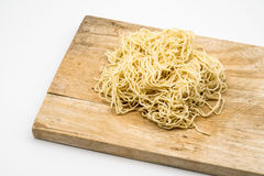 Uncooked Chinese egg noodle on wooden board Stock Image