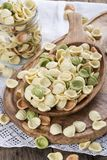 Uncooked colorful orecchiette in a wooden bowl. stock photos