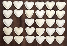 Uncooked dough in the shape of a heart dumplings, ravioli, pelmeni, laid out in rows Stock Images