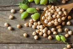 Uncooked dried chickpeas in wooden spoon with raw green chickpea pod plant on wooden table. Heap of legume chickpea background stock photo