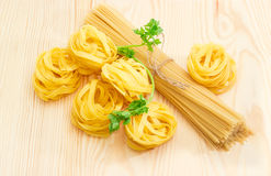 Uncooked dried pasta tagliatelle, long pasta and sprig of parsle Stock Images