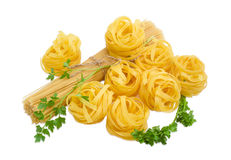 Uncooked dried pasta tagliatelle, long pasta and sprigs of parsl Royalty Free Stock Photos