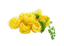 Uncooked dried pasta tagliatelle and sprig of parsley Stock Images