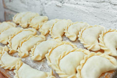 Uncooked dumplings on the kitchen board Royalty Free Stock Image