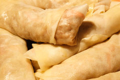 Uncooked Egg rolls. Big pile of Uncooked Egg rolls golden in color Royalty Free Stock Image