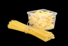 Uncooked farfalle pasta in plastic tray and long pasta Royalty Free Stock Image