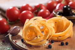 Uncooked fettuccine pasta on wooden board Royalty Free Stock Photo