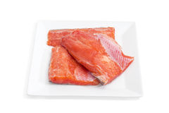Uncooked fillet of rainbow trout on a square dish closeup. Several pieces of fresh uncooked fillet of rainbow trout on a square dish on a light background Royalty Free Stock Photos