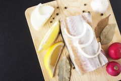 Uncooked food on wooden cutting board. Seafood and healthy fresh ingredients from vegetables. Top view and copy space on black bac. Kground Royalty Free Stock Photography