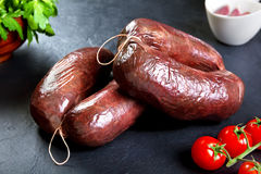 Uncooked fresh blood sausage with parsley and tomato. raw pork with cherry tomatoes Royalty Free Stock Image