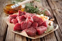 Uncooked fresh diced seasoned meat with herbs stock photography