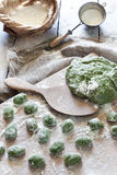 Uncooked fresh homemade spinach dumplings on wooden board with dough and flour Royalty Free Stock Images