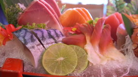 Uncooked fresh salmon and red tuna fish and saba and squid and crab with vegetable and fruits set pieces served. Over wooden board stock video
