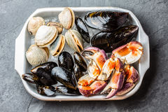 Uncooked fresh seafood Mussels, Clams, Vongole and Crabs. Uncooked raw fresh seafood - mussels, clams, vongole and crabs on ice on blac stone slate background Royalty Free Stock Photography