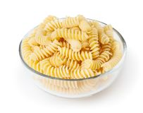 Uncooked fusilli pasta in glass bowl isolated on white royalty free stock photography