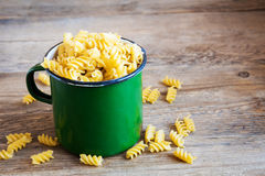 Uncooked fusilli pasta. Uncooked raw italian fusilli pasta in rustic metal mug with copy space - healthy ingredient for cooking royalty free stock images