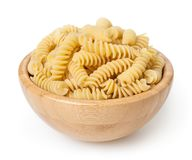 Uncooked fusilli pasta in wooden bowl isolated on white background stock photos