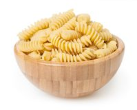 Uncooked fusilli pasta in wooden bowl isolated on white background. With clipping path stock photo