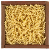 Uncooked fusilli pasta in wooden box royalty free stock photos