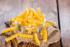 Uncooked Fussili (close-up shot). Portion of uncooked Pasta (Fussili) on rustic wooden background Royalty Free Stock Photography
