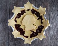 Uncooked George Washington Cherry Pie With Stars. Uncooked cherry pie with dough stars and silhouette of George Washington in a white pie pan on a dark wood Stock Photography