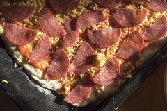 Uncooked Gourmet Salami Pizza on Square Pan. High Angle View of Uncooked Thin Crust Pizza Topped with Sliced Salami Pepperoni and Shredded Cheese - Raw Gourmet royalty free stock images
