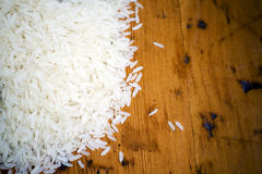 Uncooked grains of white rice. Uncooked white rice grains on a wooden surface Stock Photo