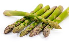 Uncooked green asparagus tips on white. Stock Photos