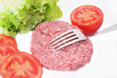 Uncooked hamburger. Uncooked salade with salade and tomatoes stock images