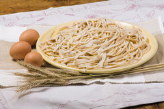 Uncooked homemade egg pasta. With mushrooms. Cut into tagliatelle stripes royalty free stock images