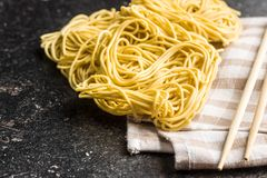 Uncooked instant chinese noodles. Uncooked instant chinese noodles and chopsticks on old kitchen table stock images