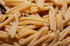 Uncooked Italian Casarecce pasta made from organic durum wheat semolina on natural olive wood cutting board. Macaroni. royalty free stock photography