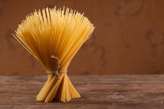 Uncooked Italian dried spaghetti tied with string. Stock Photos