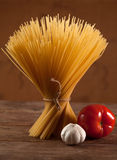 Uncooked Italian dried spaghetti tied with string. Royalty Free Stock Images