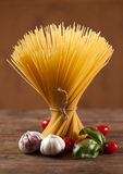 Uncooked Italian dried spaghetti tied with string, standing upright on a wooden table. Royalty Free Stock Images