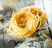 Uncooked Italian linguine or tagliatelli pasta Stock Image