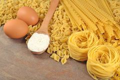 Uncooked Italian pasta, flour and eggs Stock Photo