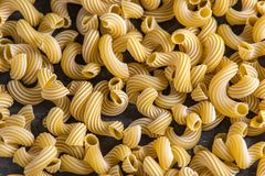 Uncooked italian pasta in the form of spirals on a dark background. Concept of composition of food design. Uncooked italian pasta in the form of spirals on a stock image