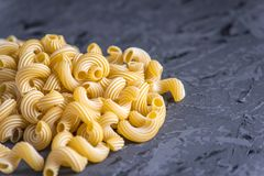 Uncooked italian pasta in the form of spirals on a dark background. Concept of composition of food design. Uncooked italian pasta in the form of spirals on a stock photography