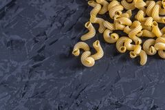 Uncooked italian pasta in the form of spirals on a dark background. Concept of composition of food design. Uncooked italian pasta in the form of spirals on a stock images