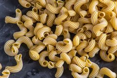 Uncooked italian pasta in the form of spirals on a dark background. Concept of composition of food design. Uncooked italian pasta in the form of spirals on a stock photo