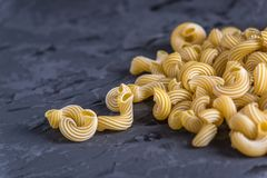 Uncooked italian pasta in the form of spirals on a dark background. Concept of composition of food design. Uncooked italian pasta in the form of spirals on a royalty free stock image