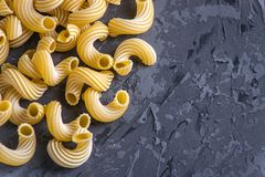 Uncooked italian pasta in the form of spirals on a dark background. Concept of composition of food design. Uncooked italian pasta in the form of spirals on a royalty free stock photo