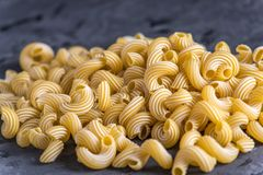 Uncooked italian pasta in the form of spirals on a dark background. Concept of composition of food design. Uncooked italian pasta in the form of spirals on a royalty free stock photos