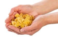 Uncooked italian pasta in hands Stock Image