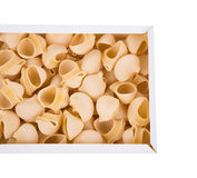Uncooked italian pasta lumaconi in cardboard box. Stock Photo
