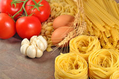 Uncooked Italian pasta, ripe tomatoes branch, garlic and eggs Stock Photos