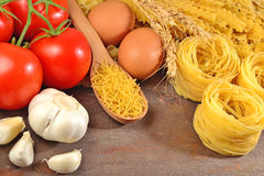 Uncooked Italian pasta, ripe tomatoes branch, garlic and eggs Royalty Free Stock Photo